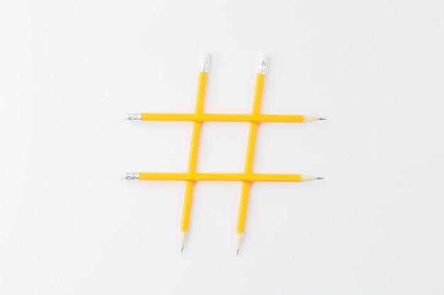 Gele potloden gevouwen in de vorm van een hashtag