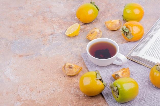 Gele pruim dadels en schijfjes citroen met een kopje thee.