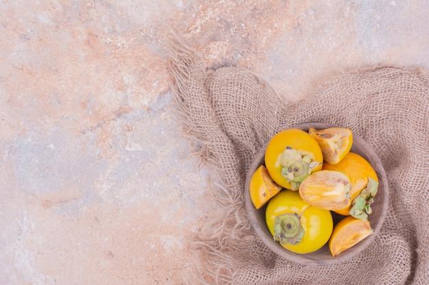 Gele pruimdata in een houten bakje.