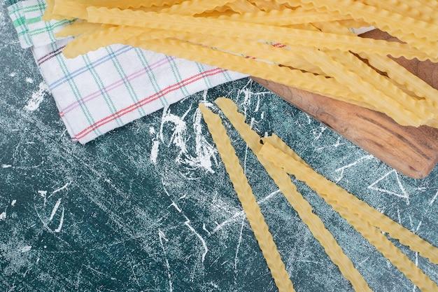 Gele rauwe pasta met tafelkleed op blauwe ruimte.