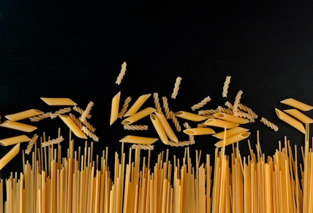 Gele rauwe zelfgemaakte spaghetti en penne pasta op een zwarte betonnen ondergrond