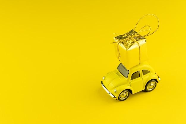 Gele retro auto met gouden geschenkdoos op een dak