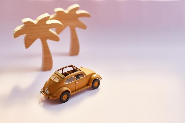 Gele retro cabriolet stuk speelgoed auto en palmen op een roze achtergrond