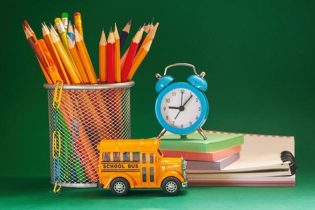 Gele retro schoolbus en potloden in een mand