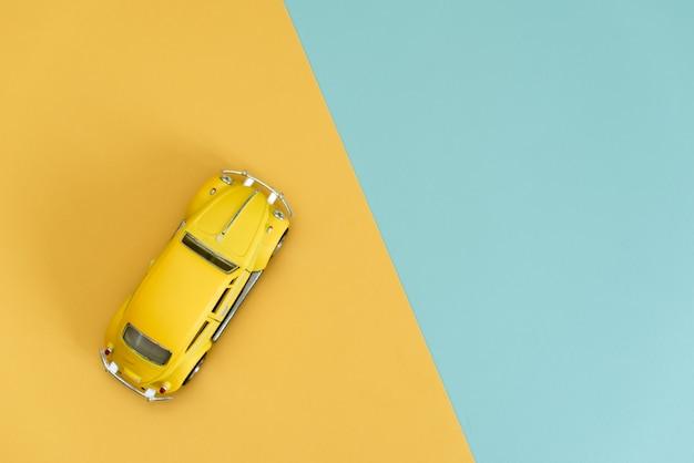 Gele retro stuk speelgoed auto op geel