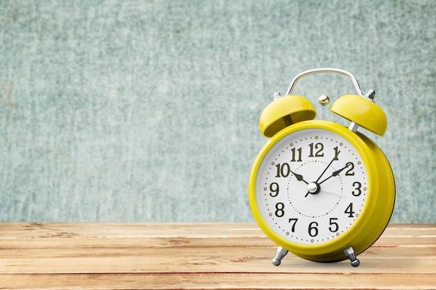 Gele retro wekker op houten tafel en muur achtergrond