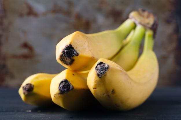 Gele rijpe bananen op rustieke tafel