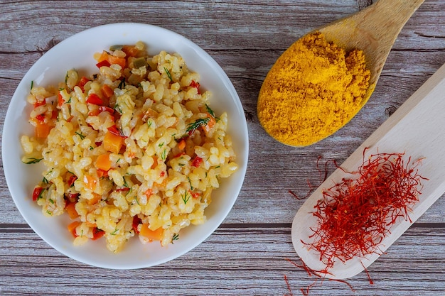 Gele rijst met groenten, saffraan, kurkuma op een witte plaat op een houten ondergrond.