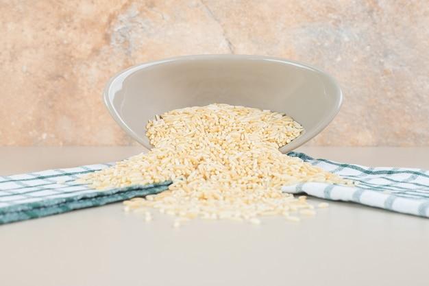 Gele rijstzaden in een kop op beton.