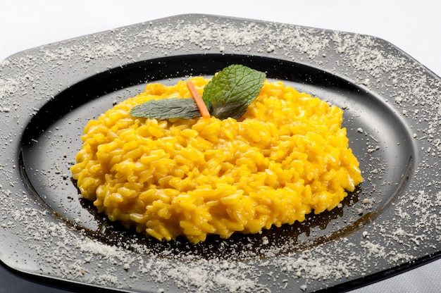 Gele risottorijst die met wortel en munt wordt versierd
