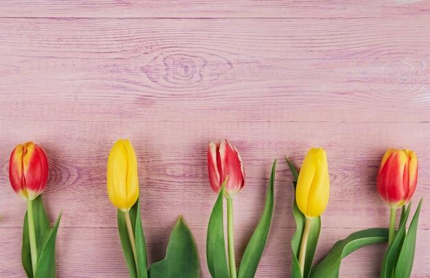 Gele, rode en roze tulpen op een roze houten achtergrond kopiëren ruimte.