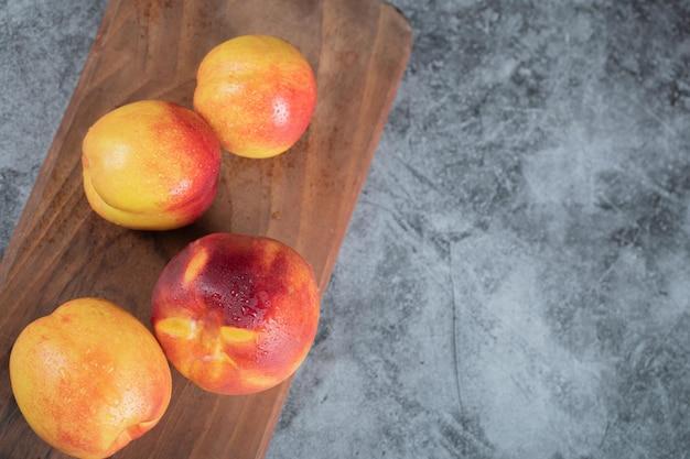 Gele rode perziken op een houten bord.