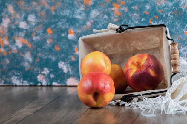 Gele roodachtige perziken op een stuk jute op tafel.