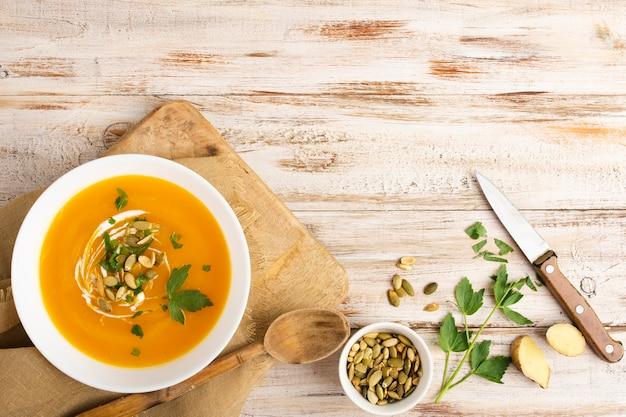 Gele roomsoep met zaden en mes naast