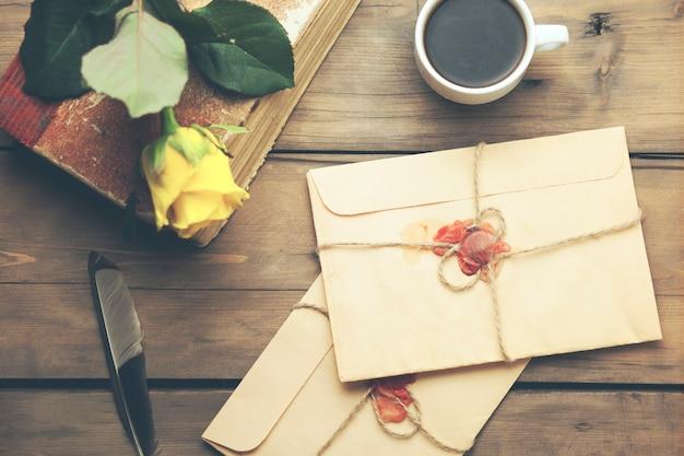 Gele roos met letters, boek en koffie op tafel