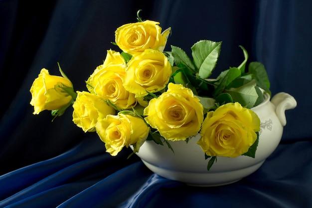 Gele rozen in een brede vaas op een blauwe achtergrond