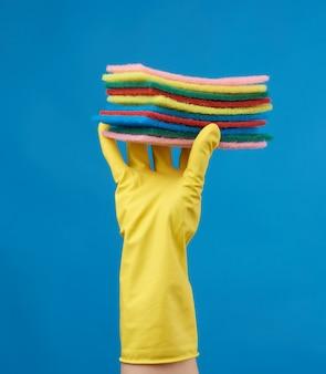 Gele rubberen handschoen om schoon te maken wordt op zijn hand gelegd, een deel van het lichaam wordt opgetild