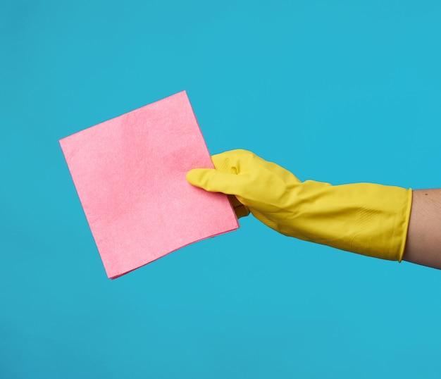 Gele rubberen handschoen voor het schoonmaken wordt op zijn hand gelegd en houdt een keuken roze sponzen