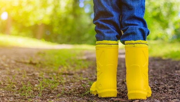Gele rubberen laarzen aan de voeten van het kind. schoenen voor nat weer.