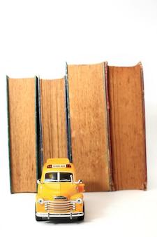 Gele schoolbus speelgoed model en oude boeken. vintage achtergrond.