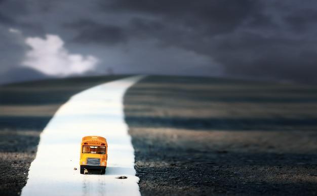 Gele schoolbus speelgoed model op landweg. zeer ondiepe scherptediepte samenstelling.