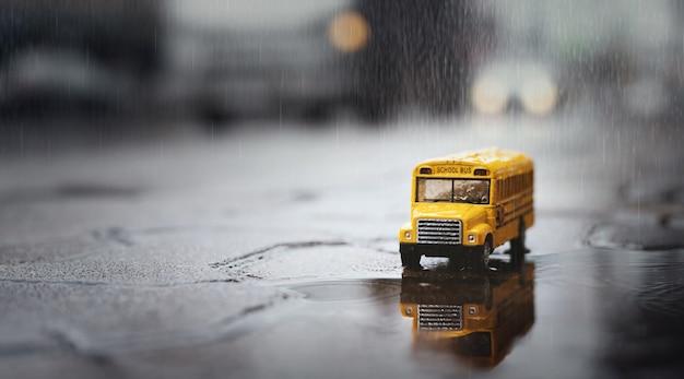 Gele schoolbus (speelgoedmodel) tijdens harde regenval in stad, lage hoekmening en ondiepe scherptediepte van veldsamenstelling.