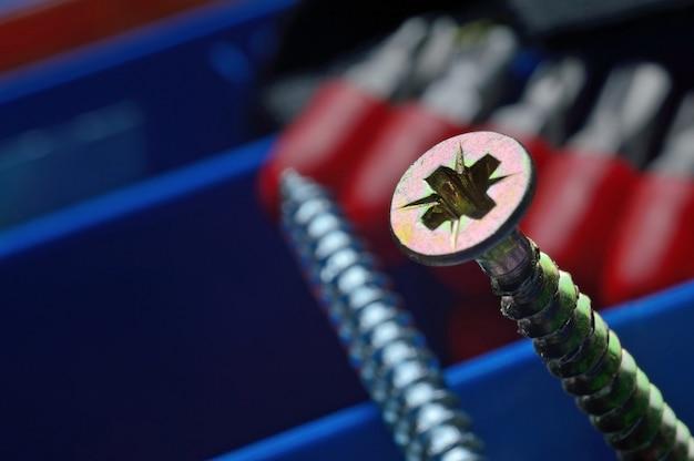 Gele schroeven in een plastic gereedschapskist met een schroevendraaier