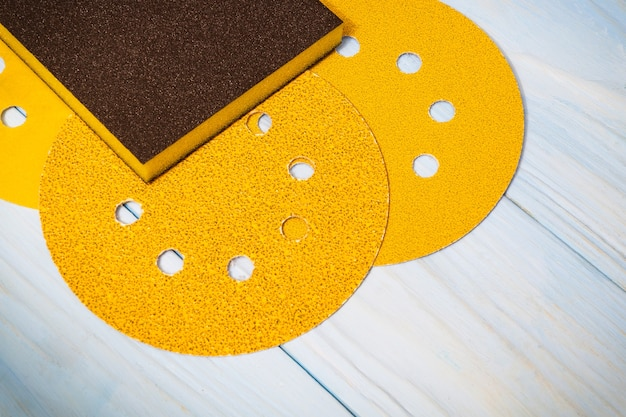 Gele schuurmiddelen op houten blauwe planken