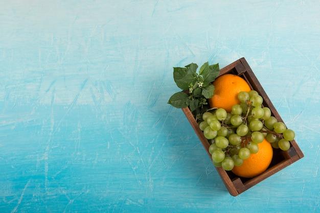 Gele sinaasappelen en een bos druiven in een houten kist