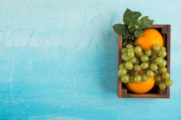 Gele sinaasappels en een tros druiven in een houten kist in het midden