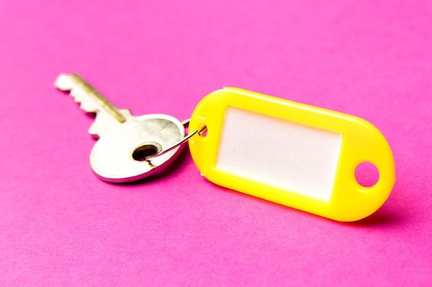 Gele sleutelhanger op een paars getextureerd karton