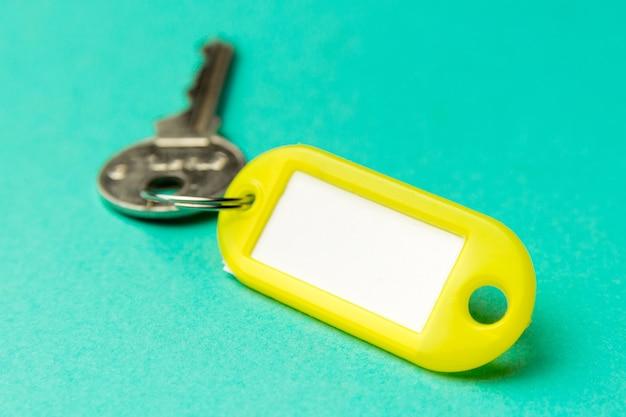 Gele sleutelhanger op een turkoois gestructureerd karton