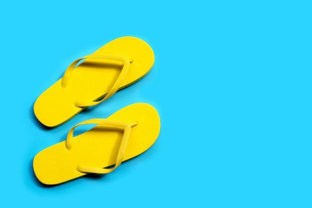 Gele slippers op blauwe achtergrond.