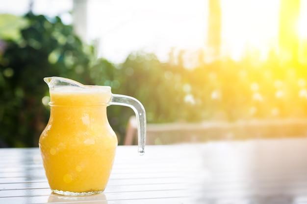 Gele smoothie van tropisch fruit op de witte houten tafel in kruik op zonnige dag