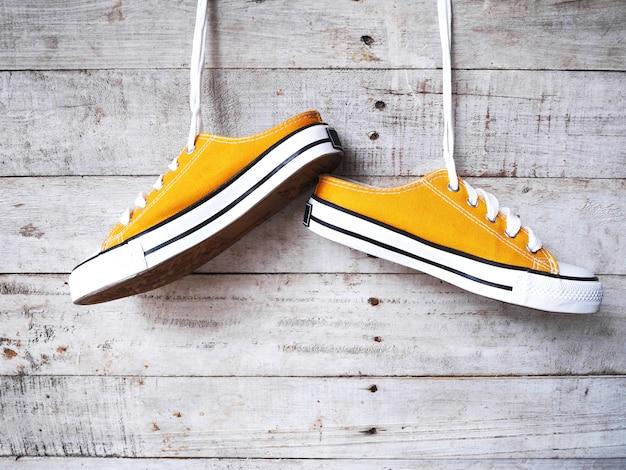 Gele sneakers schoenen met witte schoenveter opknoping over vintage hout.