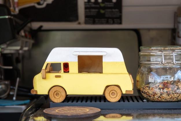 Gele speelgoed vintage bestelwagen op de teller van de voedselvrachtwagen. houten model van retro auto in mobiele coffeeshop.