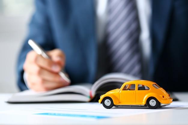 Gele speelgoedauto bij de verkoop van documenten