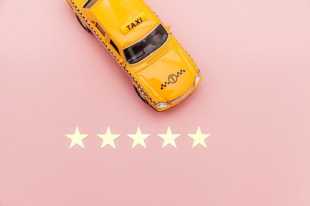 Gele speelgoedauto taxi cab en 5 sterren waardering geïsoleerd op roze achtergrond