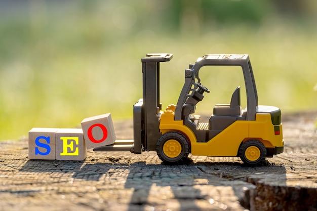 Gele speelgoedvorkheftruck houdt letterblok o om woord seo (afkorting van zoekmachineoptimalisatie) op houten tafel te voltooien