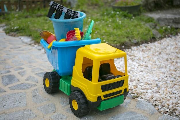 Gele speelgoedvrachtwagen in de tuin
