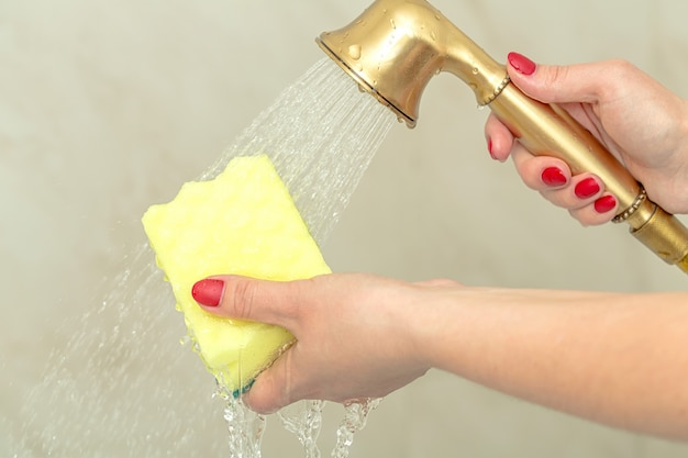 Gele spons in een vrouwelijke hand