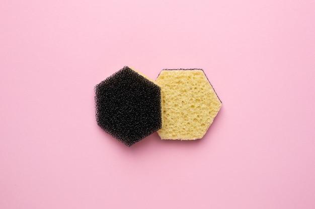 Gele sponzen voor het afwassen op een roze achtergrond