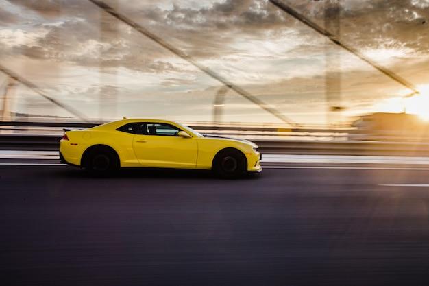 Gele sportcoupé op de weg in de zonsondergang.