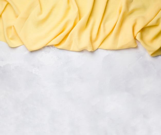 Gele stof valt van bovenaf op een betonnen witte ruimte. kopieer ruimte