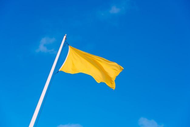 Gele stoffenvlag die aan de wind met de achtergrond van een duidelijke hemel met witte wolken golft.