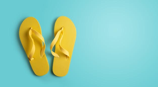 Gele strand pantoffels geïsoleerd op blauw