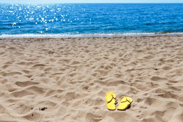 Gele strandpantoffels op zandstrand, zomer, baden