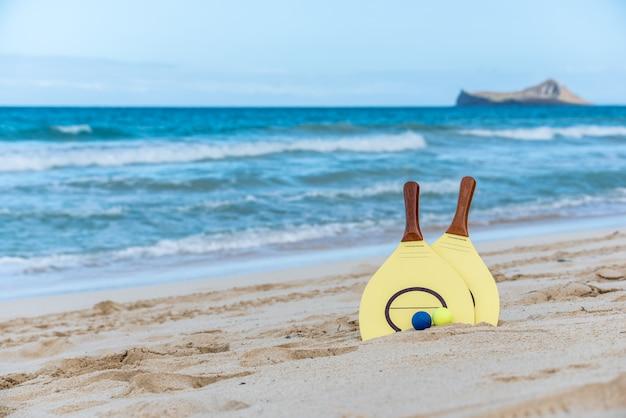 Gele strandpeddel en ballen op een zandig strand in hawaï met golven en een eiland op de achtergrond