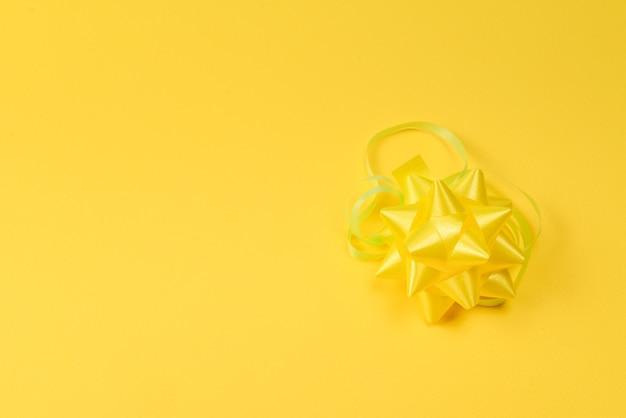 Gele strik op een gele achtergrond. ruimte kopiëren.