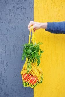 Gele string tas met komkommers, tomaten, bananen en kruiden in de hand close-up. heldere foto in rode, gele, groene tinten. duurzaamheid, nul afval, plasticvrij concept, vegetarisme, gezonde voeding.